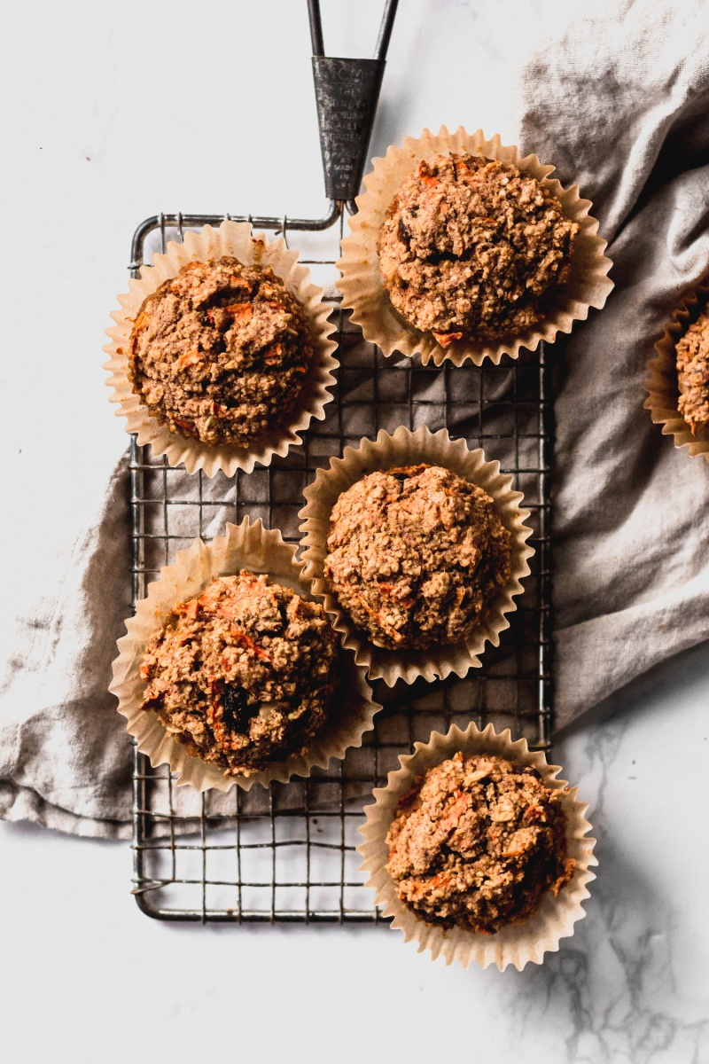 five vegan oat muffins on wire rectangular board with grey cloth in background