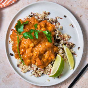 a plate of grains topped with pumpkin curry served with two lime wedges