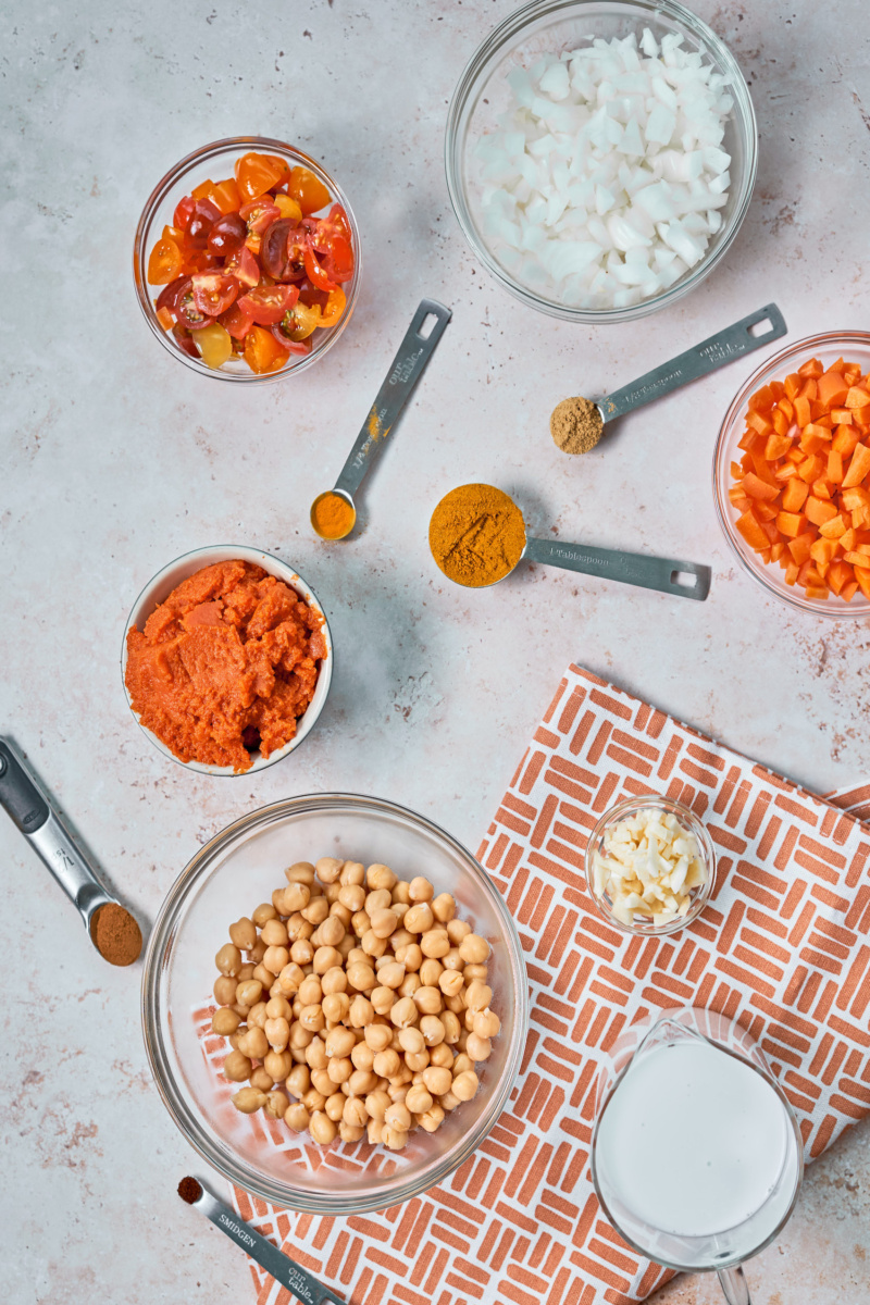 a bowl of onions, a bowl of tomatoes, a bowl of diced carrots, a cup of pureed pumpkin, a bowl of chickpeas, a cup of minced garlic, a measuring cup of coconut and measuring spoons full of spices, all resting on a countertop