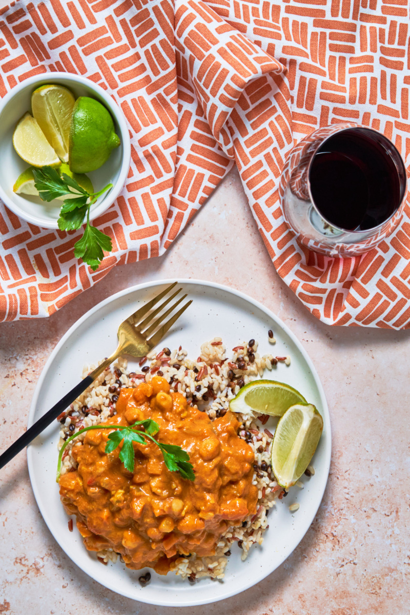 a plate of chickpea pumpkin curry served over a grain blend with lime wedges and a glass of red wine