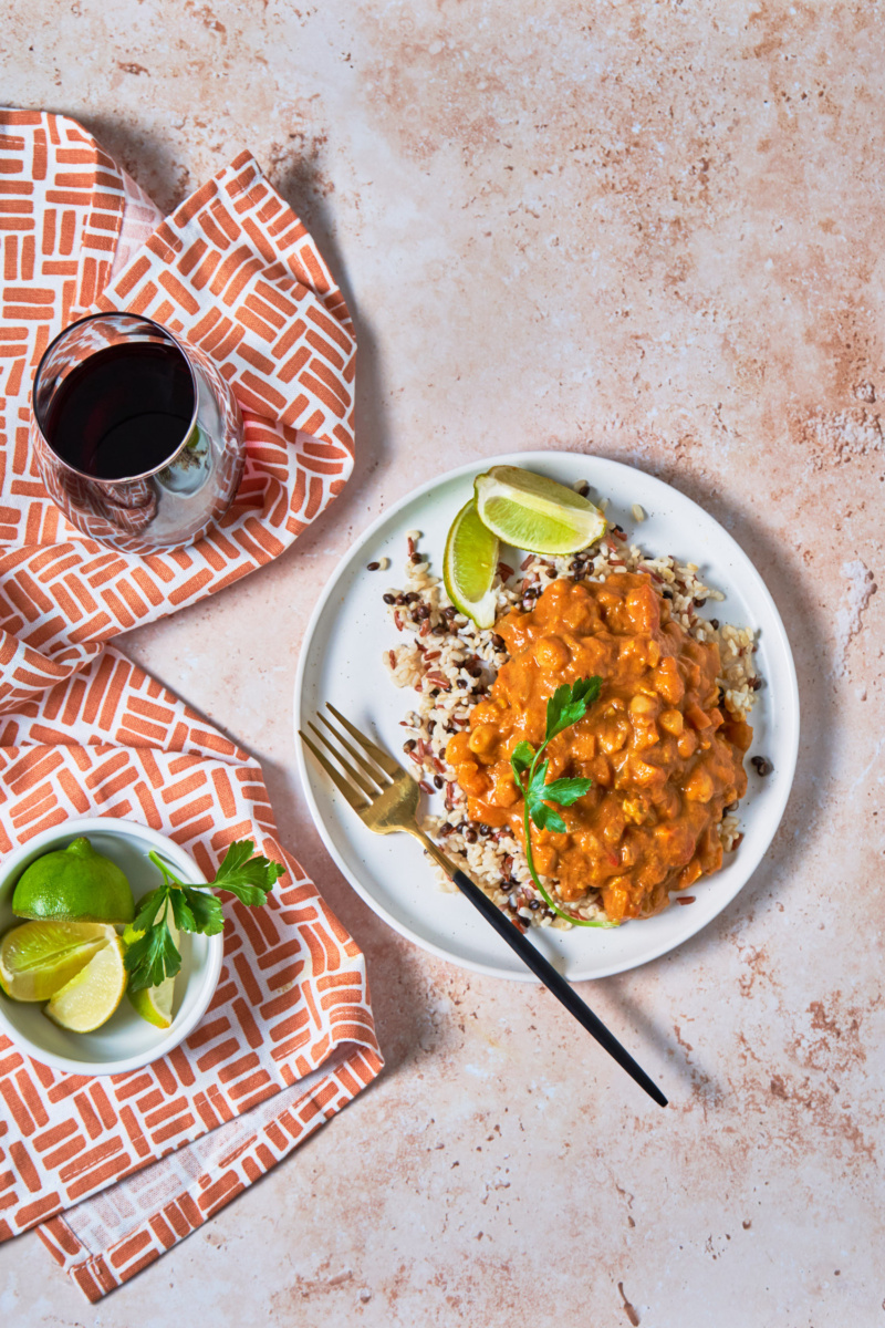 a plate of grains topped with coconut pumpkin curry served with lime wedges