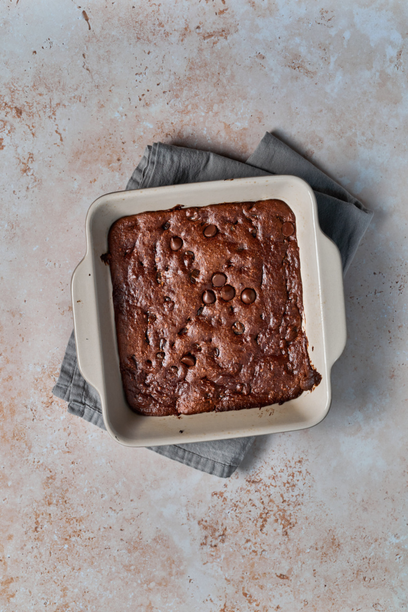 a tray of almond butter chocolate chip blondies resting on a dish towel