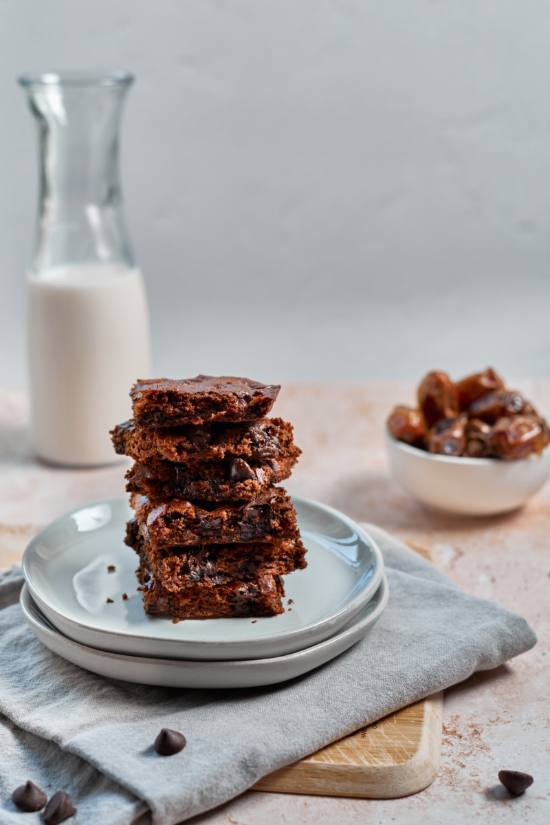 a plate of almond butter chocolate chip blondies stacked on top of one another with a jug of milk and bowl of dates in the background