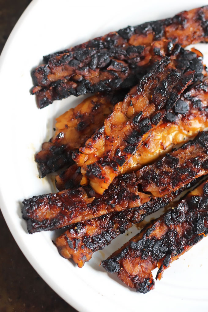 a plate of tempeh bacon strips