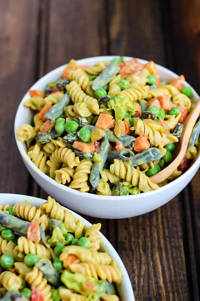 two bowls of vegan pasta salad with veggies and a curried tofu sauce