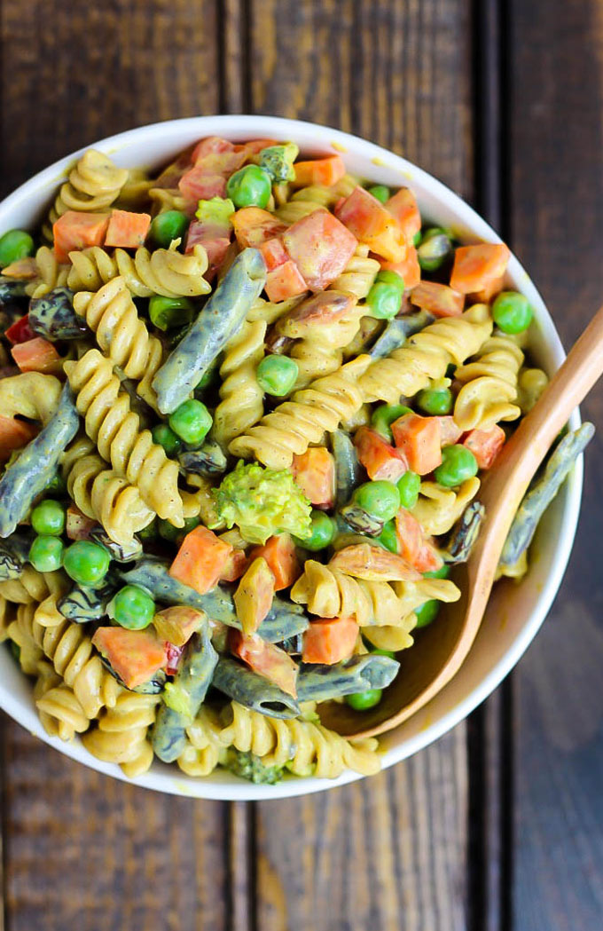 a bowl of vegan pasta salad with legume pasta, green beans, bell pepper, peas, broccoli and a silken tofu curry sauce