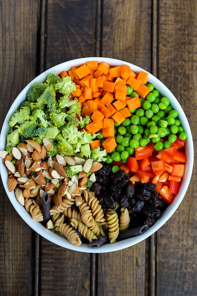 A bowl of vegan pasta salad before it's mixed, containing chopped almonds, raw broccoli, carrots, green peas, red bell pepper, legume pasta and raisins