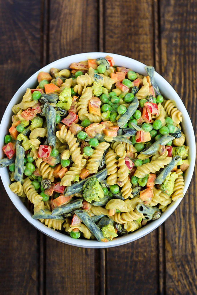 An overhead shot of a large bowl of vegan pasta salad with green beans, peppers, peas, carrots and broccoli with a curry sauce