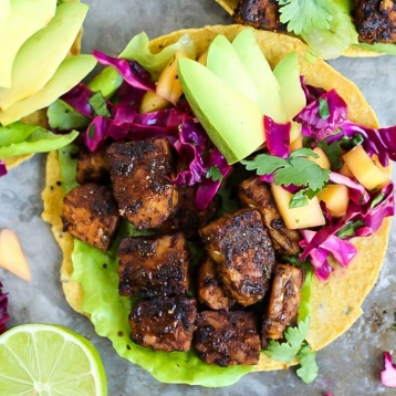 A smoky tempeh tostada topped with mango cabbage slaw and sliced avocado