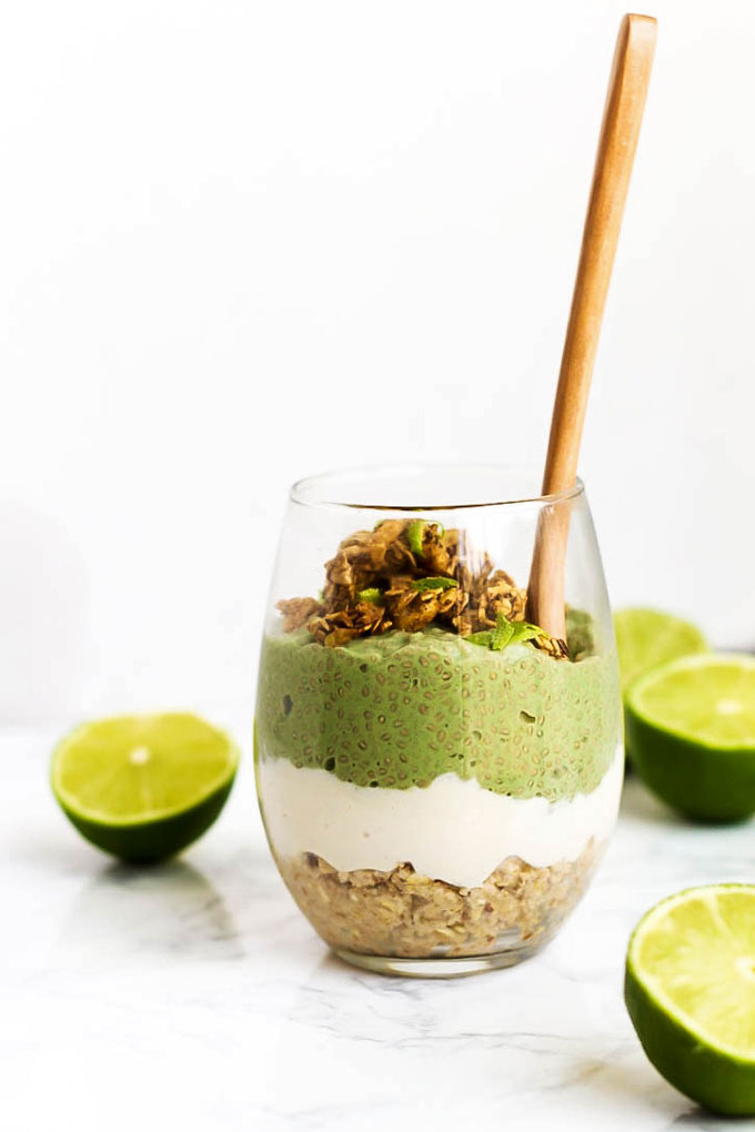 a vegan parfait served in a clear glass featuring lime chia pudding, oat crust and vanilla vegan pudding, all surrounded by halved limes