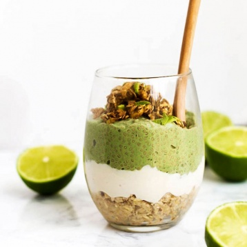 a vegan chia pudding parfait with a layer of oat crust at the bottom, a vanilla pudding in the middle and a green lime-flavored chia pudding on top