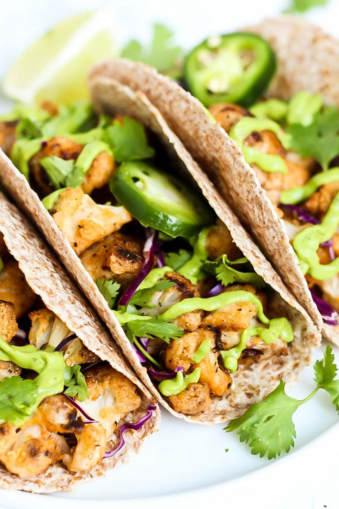 These Vegan Buffalo Cauliflower Tacos with Avocado Cilantro Sauce are PACKED with flavor & a healthy option for taco night! Vegan, gluten-free & delicious.