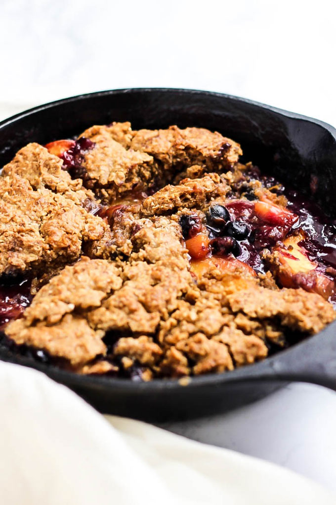 Dig into this Vegan Peach Blueberry Cobbler & enjoy every sweet, delicious bite! A piece of this gluten-free cobbler is perfect with a scoop of ice cream.