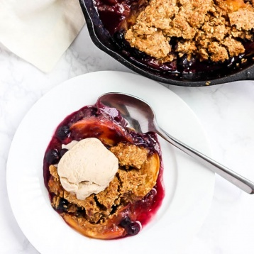 A cast iron skillet of peach and blueberry cobbler next to a serving of the cobbler in a white bowl served with a scoop of vanilla vegan ice cream