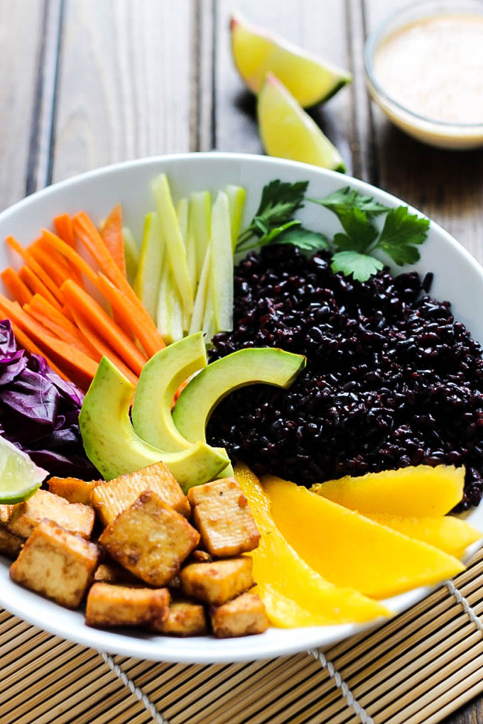 A power bowl filled with black rice, sriracha tofu, mango, vegetables and served with limes