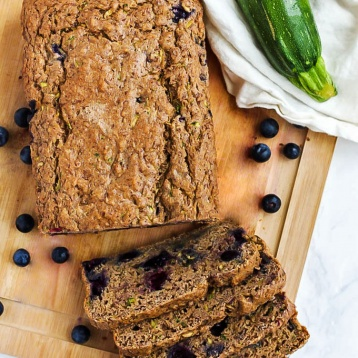 An overhead shot of a blueberry zucchini loaf and four cut slices resting on a wooden cutting board, surrounded by blueberries and a zucchini