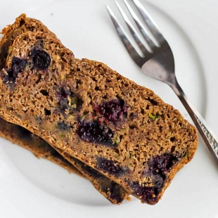 A slice of blueberry zucchini bread served on a white plate with a silver fork
