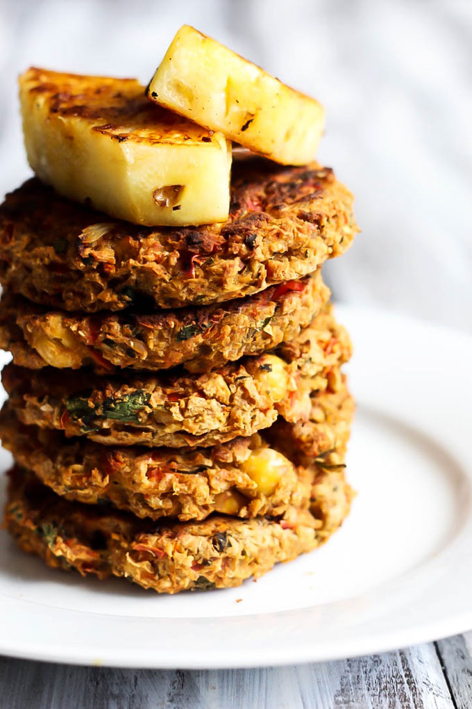 A stack of chickpea veggie burgers topped with two wedges of grilled pineapple