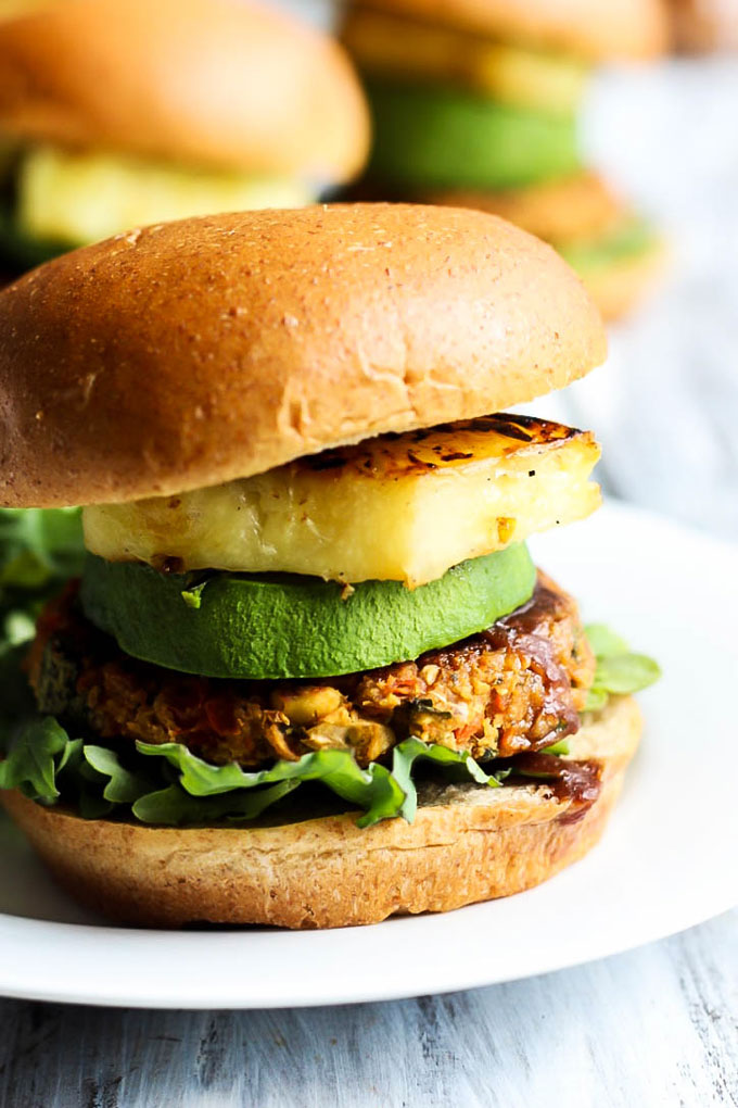 A vegan chickpea patty served on a bun with lettuce, bbq sauce, avocado and grilled pineapple