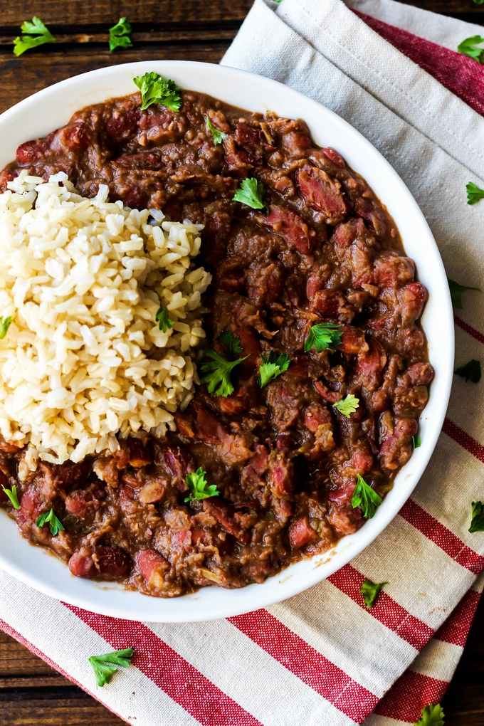 A white bowl of cajun-style vegan red beans served with rice is placed on a dark wooden table with a red and white stripped napkin, surrounded by a scattering of parsley