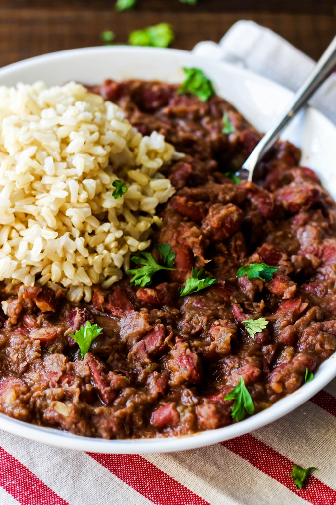 A fork digs into a bowl of vegan cajun red beans and rice