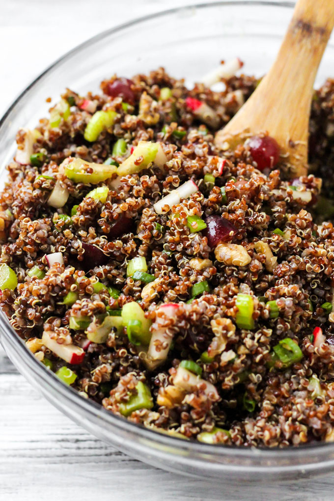 A large mixing bowl of curry quinoa salad being mixed by a wooden spoon