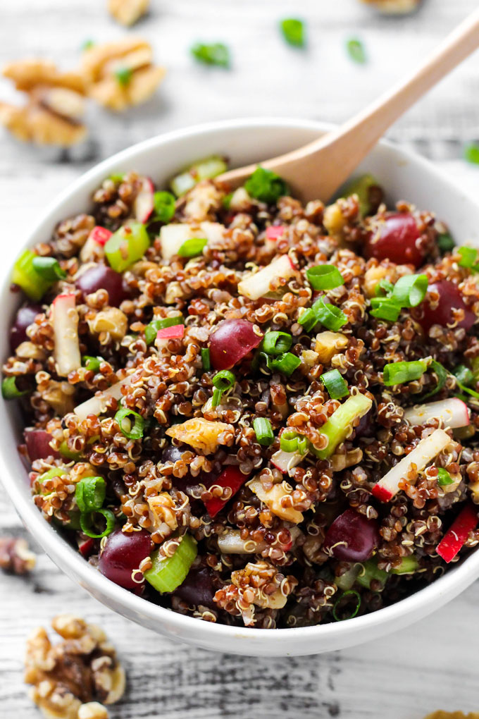 a bowl of quinoa salad including grapes, walnuts, celery, radishes, green onion and curry dressing