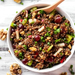 a bowl of quinoa salad with grapes, walnuts, radishes, green onions, celery and a curry vinaigrette