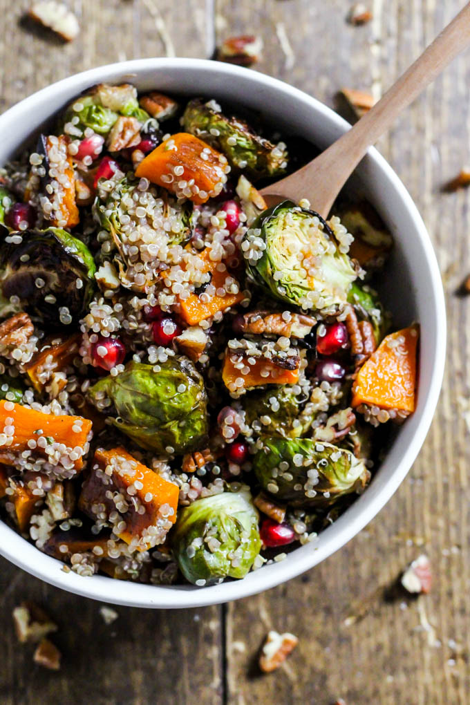 a bowl of warm brussels sprouts salad with quinoa and butternut squash topped with pomegranate seeds and pecans