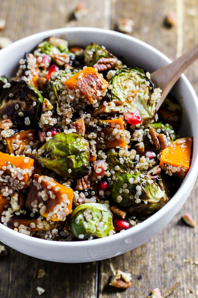 a bowl of quinoa salad with roasted veggies, pomegranate seeds and pecans