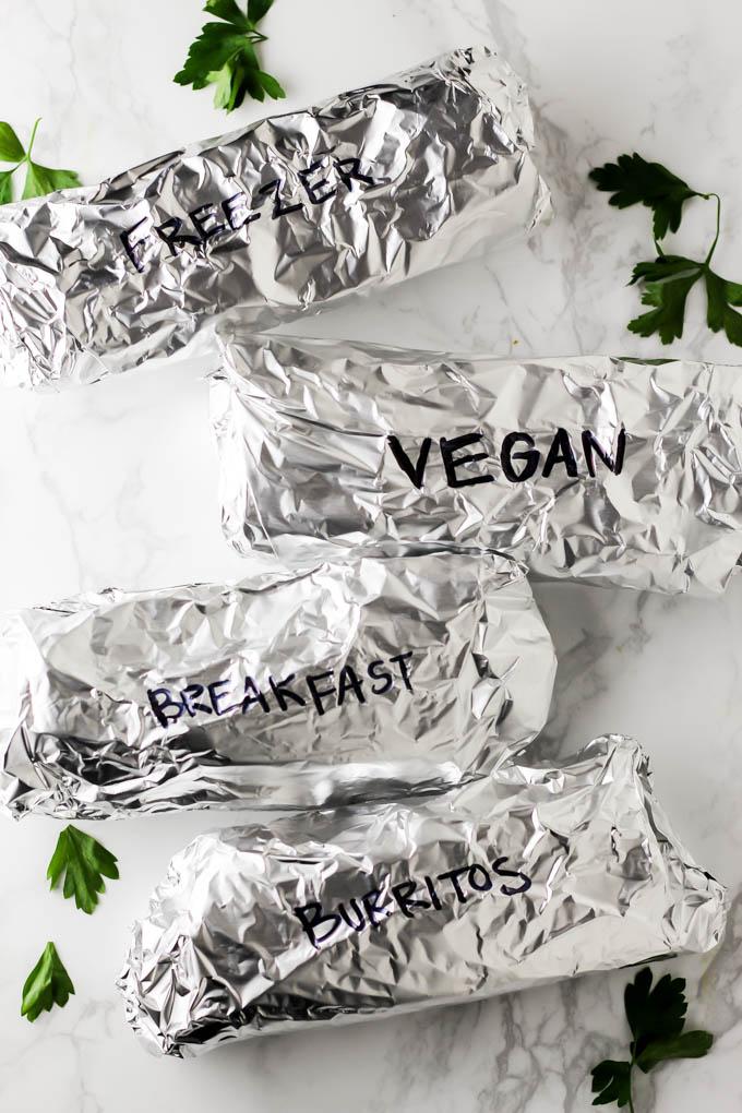 four burritos wrapped in aluminum foil