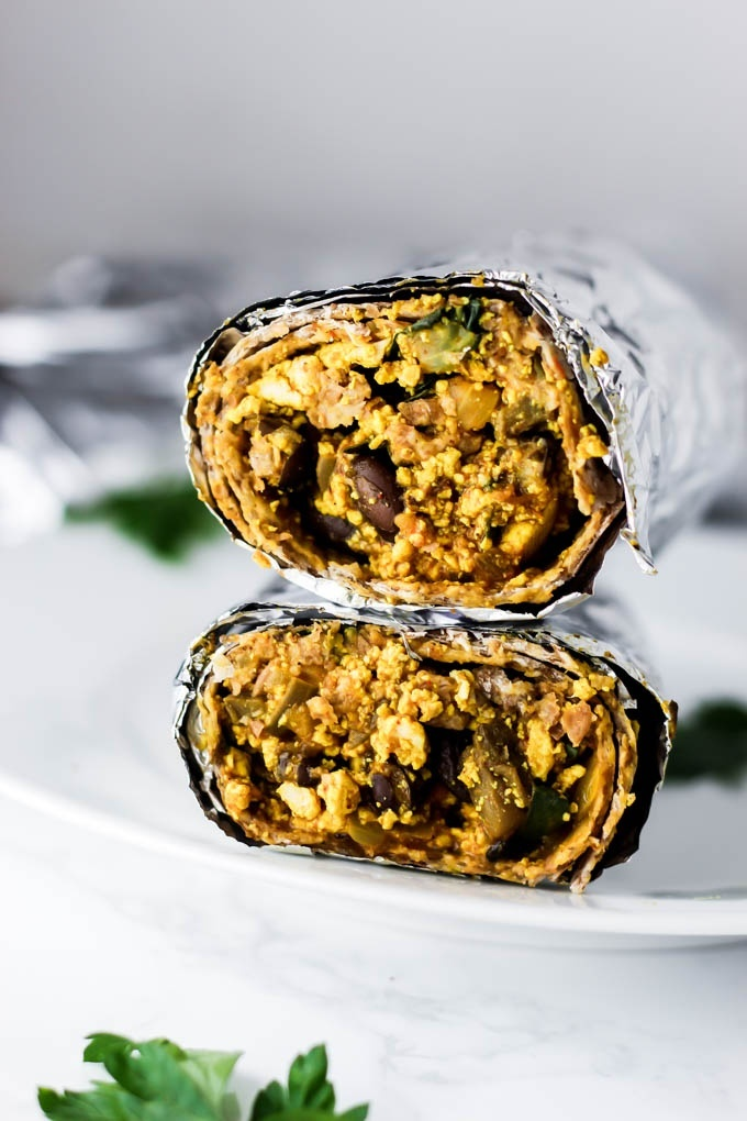 two halves of a foil-wrapped burrito stacked on top of one another