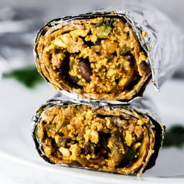 a burrito cut in half and wrapped in foil
