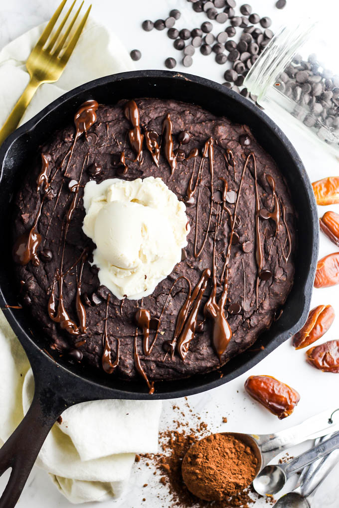 A bird's-eye shot of a cast iron skillet brownie. The skillet is surrounded by a gold fork, a jar of chocolate chips spilling onto the counter, dates and a tablespoon of cocoa powder. The brownie is topped with vanilla vegan ice cream and a drizzle of chocolate