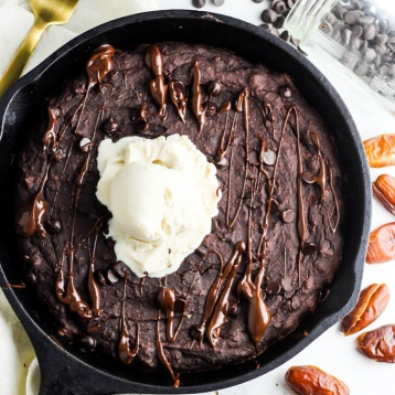 A close up of a baked brownie served in a cast iron skillet, drizzled with melted chocolate and topped with vanilla dairy-free ice cream