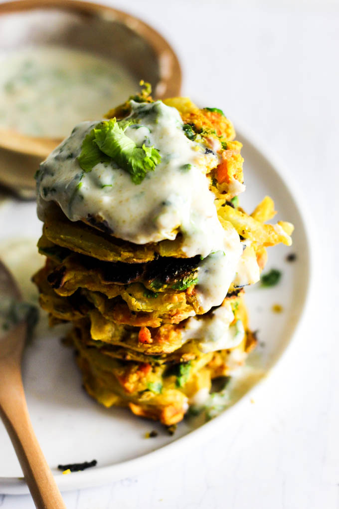 Add these Crispy Onion & Carrot Fritters to dinner for a flavorful, vegetable-packed side dish! A dollop of cumin yogurt tops it off. Vegan & gluten-free!