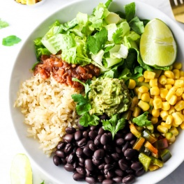 a lunch bowl filled with black beans, brown rice, salsa, lettuce, a wedge of lime, corn, peppers and a dollop of guacamole