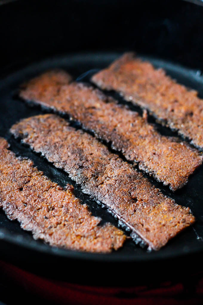 Four slices of vegan bacon being fried in a cast iron skillet