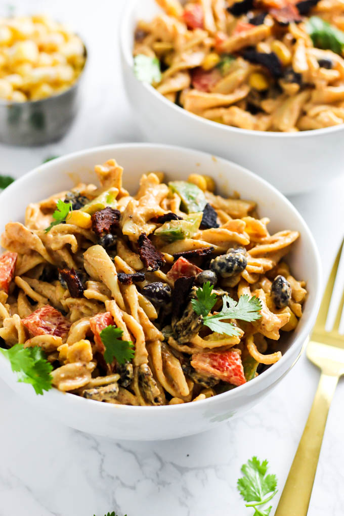 Two bowls of Mexican inspired pasta salad topped with fresh cilantro