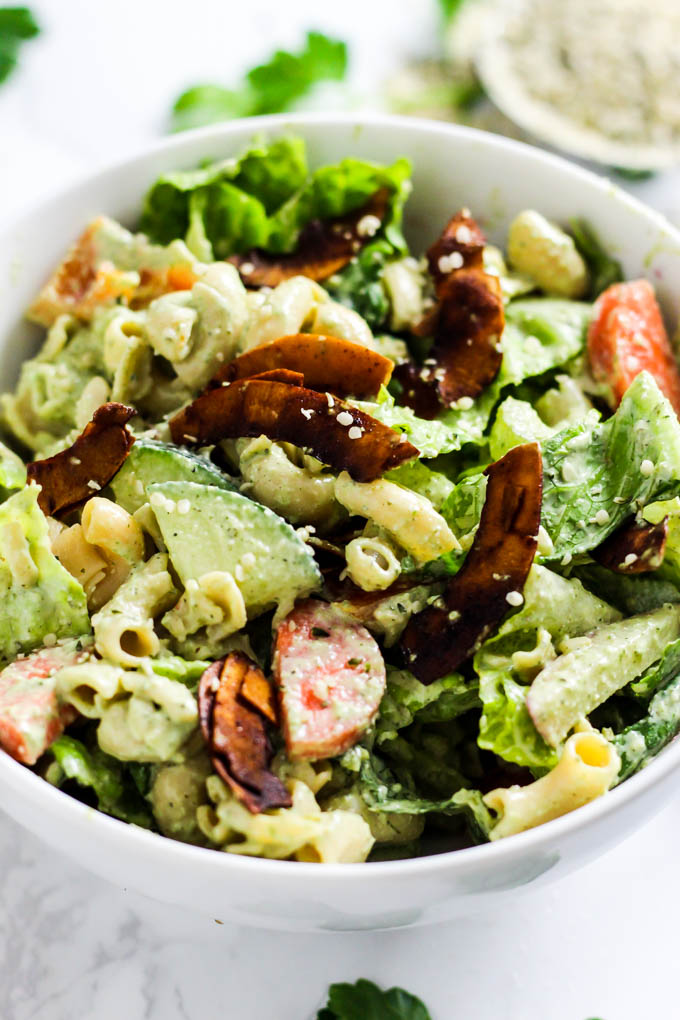 A bowl of pasta salad with lettuce, carrots, radishes, peppers, coconut bacon, pasta and dairy free ranch