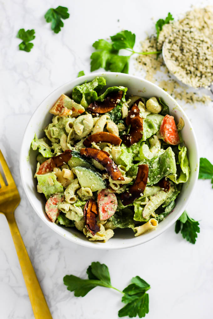 A serving of dairy-free pasta salad topped with coconut bacon and a sprinkle of hemp seeds