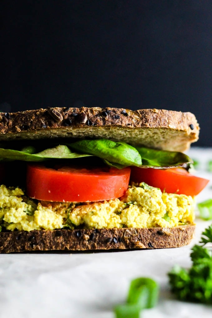 A close up of a tofu salad sandwich topped with slices of tomato and lettuce