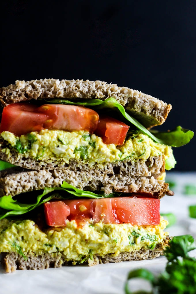 Two halves of a tofu salad sandwich stacked on top of one another