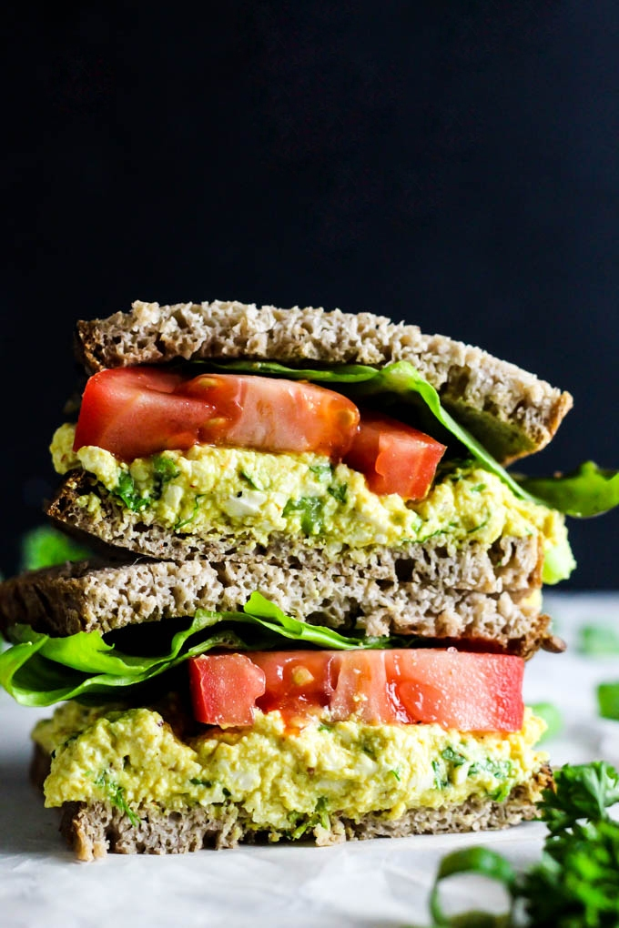 A tofu salad sandwich topped with sliced tomato and lettuce