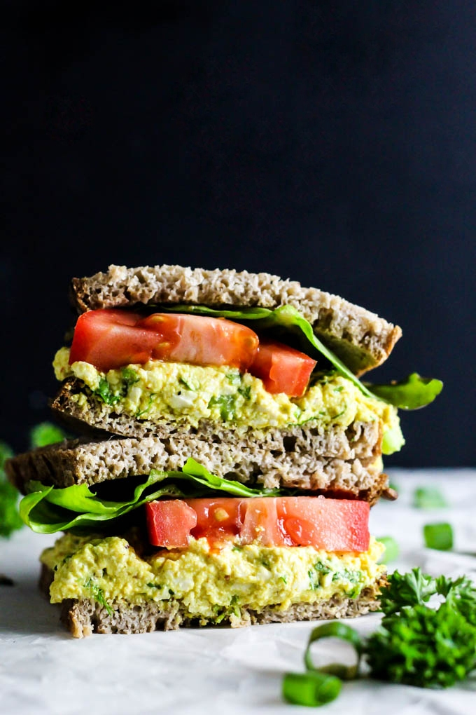 A tofu egg salad sandwich topped with lettuce and tomato