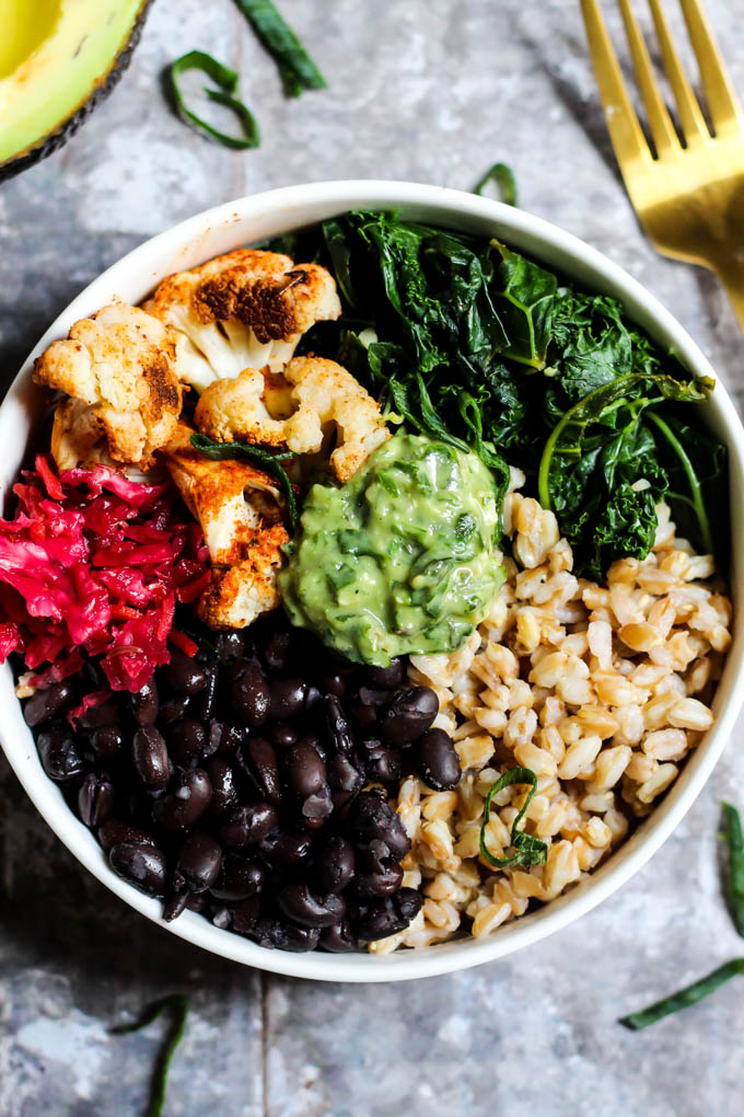 A close up shot of a power bowl made with roasted cauliflower, black beans, cooked kale, farro, sauerkraut and a dollop of homemade avocado pesto