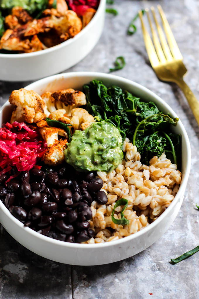A close up of a power bowl made with black beans, farro, wilted kale, cauliflower and sauerkraut served with a dollop of avocado pesto