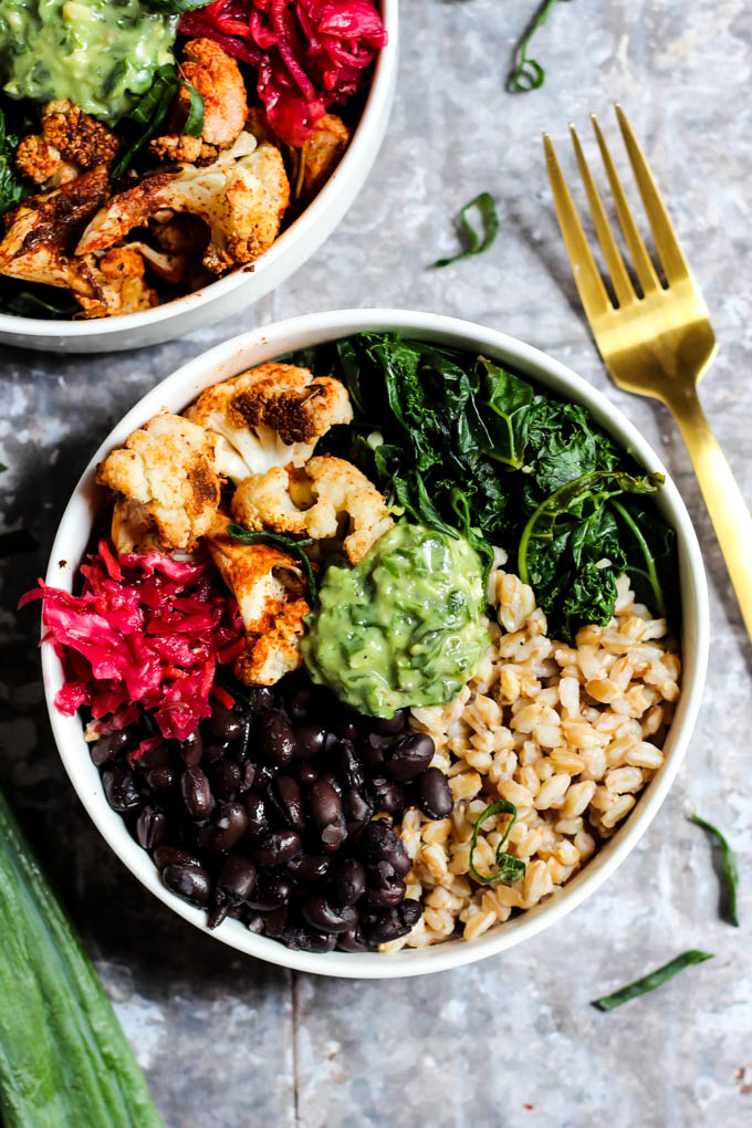 Two bowls packed with farro, black beans, sauerkraut, roasted cauliflower, wilted kale and avocado pesto