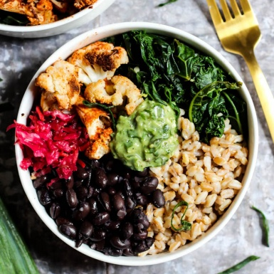 A bowl packed with farro, black beans, sauerkraut, cauliflower, wilted kale and avocado pesto