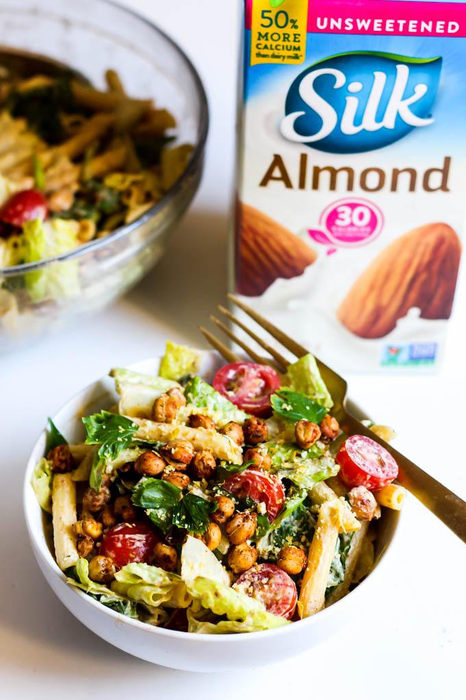A bowl of vegan pasta salad with homemade vegan caesar dressing sits next to a carton of almond milk